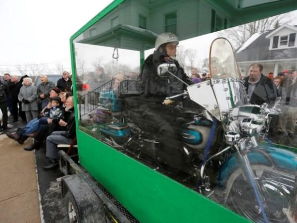 Homem enterrado junto a uma Harley Davidson